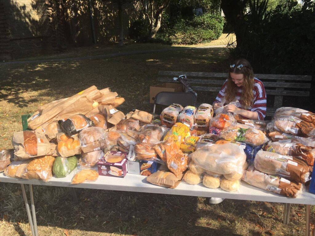Woman with lots of food and bread by the community fridge on tour in Angmering